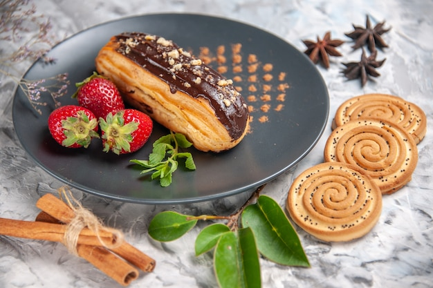 Front close view yummy choco eclairs with cookies on light table biscuit cake dessert
