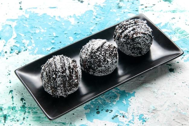Вид спереди крупным планом вкусные шоколадные шарики, шоколадные торты с глазурью на синей поверхности, выпечка бисквита, сладкий сахар, шоколад