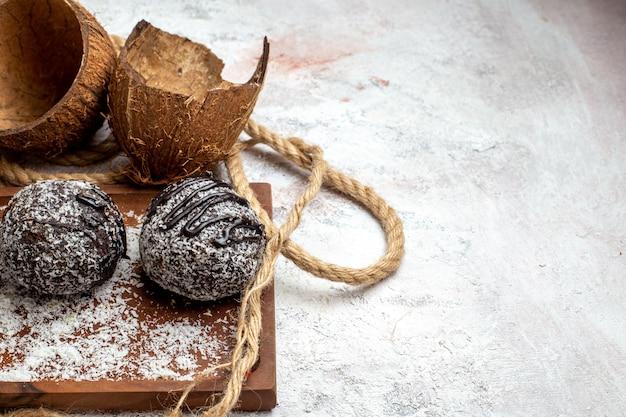 밝은 흰색 표면에 코코넛과 함께 전면 닫기보기 맛있는 초콜릿 케이크 비스킷 설탕 케이크 달콤한 쿠키 초콜릿