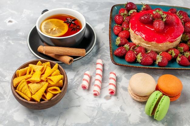 Torta di fragole gustosa vista ravvicinata frontale con tazza di tè e macarons di fragole rosse fresche su superficie bianca