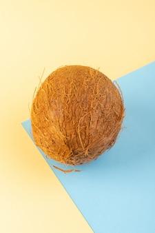 Un frontale chiuso vista noci di cocco intero latteo fresco dolce isolato su sfondo color crema-blu ghiacciato frutta esotica tropicale dado