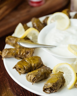 A front closed-up view dolma with yogurt and lemon slices inside plate