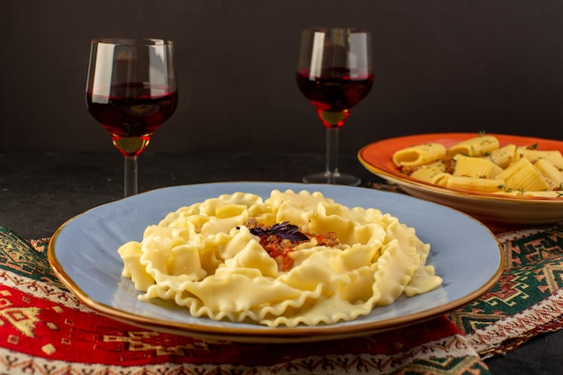 A front closed up view dough pasta cooked tasty salted inside round blue plate with glasses of wine on designed carpet and dark desk