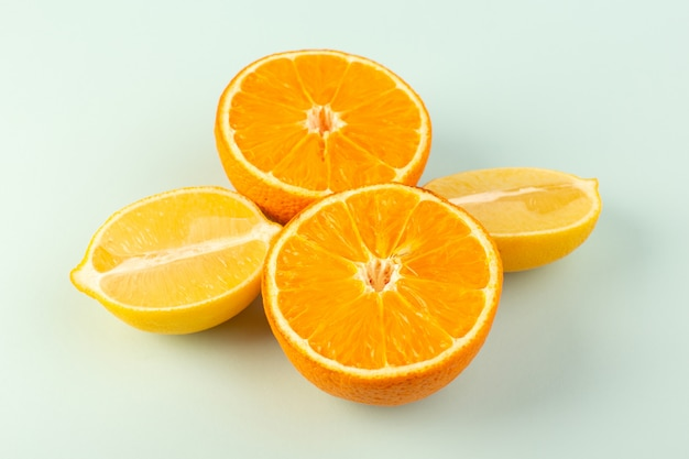 A front closed up view sliced orange fresh ripe juicy mellow isolated half cut pieces along with sliced lemons