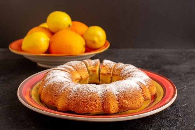 A front closed up view sweet round cake with sugar powder sliced sweet delicious isolated cake inside plate along with lemons and grey background biscuit sugar cookie