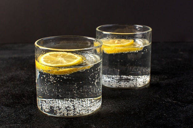 A front closed up view water with lemon fresh cool drink with sliced lemons inside transparent glasses