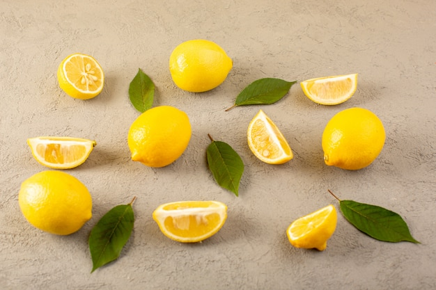 A front closed up view yellow fresh lemons ripe mellow and juicy whole and sliced with green leaves lined on the grey
