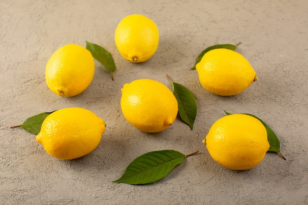 A front closed up view yellow fresh lemons ripe mellow juicy with green leaves lined on the grey