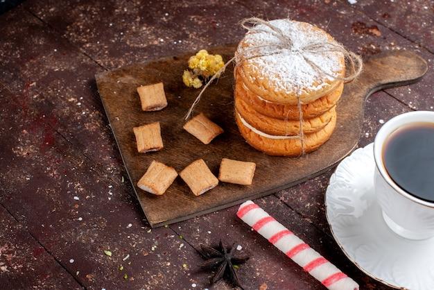 Vista ravvicinata anteriore tazza di caffè forte e caldo insieme a biscotti e biscotti sandwich su legno marrone