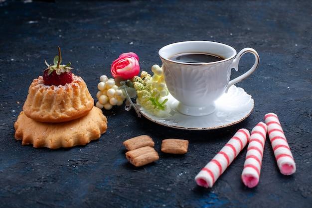 Вид спереди ближе чашка кофе с розовыми конфетами и вкусным тортом на синем