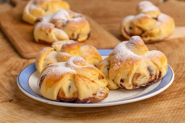 木製のテーブル、甘い砂糖のケーキベークペストリーフルーツのプレートの内側の充填とフロントクローザービューおいしいペストリー