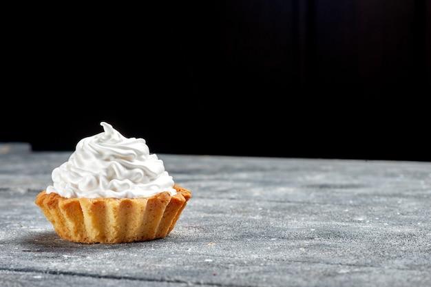 Вид спереди ближе маленький сливочный торт, испеченный вкусно изолирован на сером