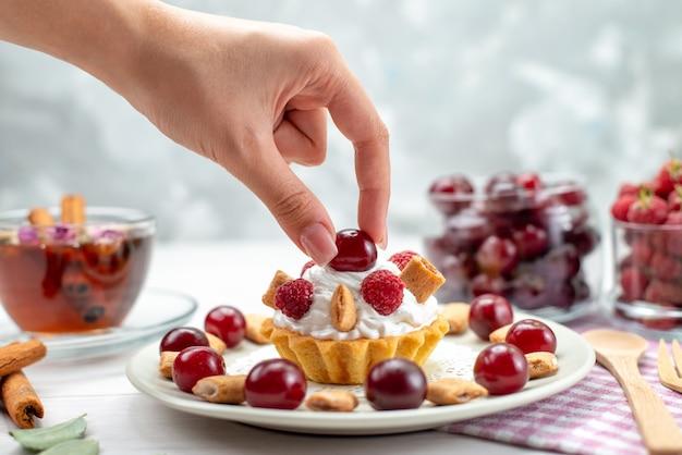 Маленький сливочный торт с малиной, вишней и маленьким печеньем, который принимает женщина на светлом столе, спереди ближе