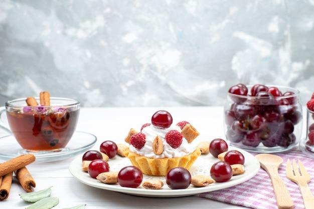 Вид спереди ближе маленький кремовый торт с малиной, вишней и маленьким печеньем, чай с корицей на светлом столе