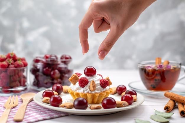 Вид спереди ближе маленький кремовый торт с малиной, вишней и маленьким печеньем, чай с корицей на белом столе