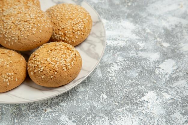 Vista più ravvicinata anteriore piccoli biscotti morbidi delizioso dessert per il tè sulla superficie bianca torta di biscotti cuocere i biscotti dolci di zucchero
