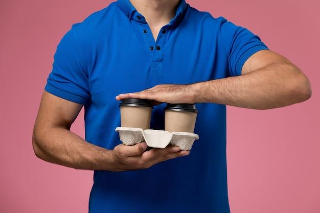 Спереди ближе вид мужчина-курьер в синей форме, держащий кофейные чашки на розовом, униформе работника службы доставки