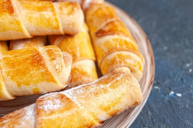 Вкусные сладкие браслеты с начинкой внутри тарелки на темном столе.
