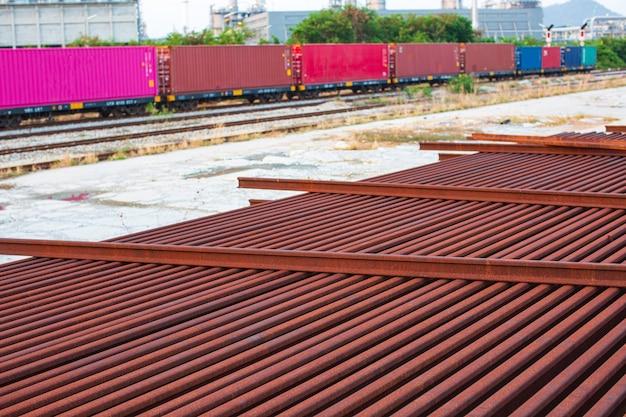 列車と鉄道のフロントコンテナは、輸出入のロジスティックコンセプトのためにこの画像を港に送るのを待っています。石油化学産業のタンク石油精製プラントとタワーカラムのシーン