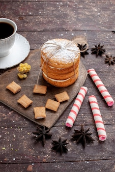 Vista in lontananza anteriore tazza di caffè forte e caldo insieme a biscotti e biscotti sandwich su legno