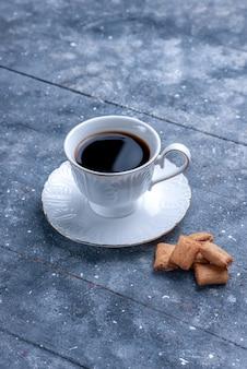 Tazza di caffè vista in lontananza frontale con biscotti a forma di cuscino sulla scrivania luminosa
