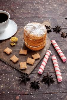 Чашка крепкого и горячего кофе спереди вдалеке вместе с печеньем и сэндвич-печеньями на дереве