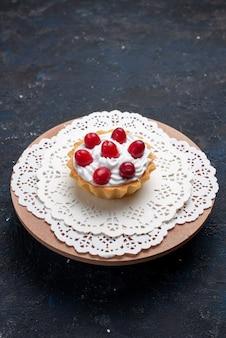 暗い表面のケーキフルーツにクリームと赤のフルーツが付いた正面の遠景のおいしいケーキ