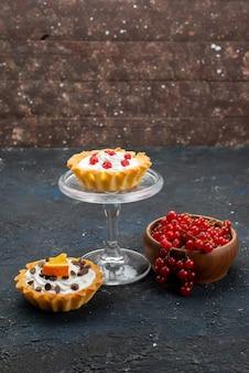 暗い表面の甘いベリーにクリームとフルーツが入った正面の遠くのおいしいケーキ