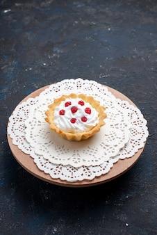 ダークブルーの表面のケーキフルーツビスケットにクリームと赤のフルーツが入った正面の遠くからのおいしいdケーキ