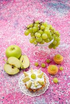 正面の遠景新鮮な緑のブドウ全体の酸っぱくておいしい果物と小さなケーキの光