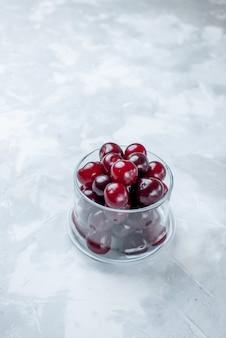 白色光の机の上の小さなガラスのコップの中の正面の遠景新鮮なサワーチェリー