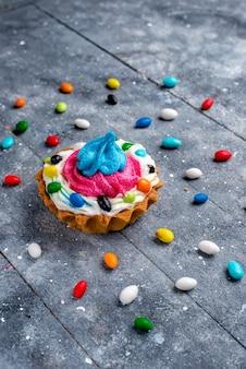 正面の遠景クリームとさまざまなカラフルなキャンディーがすべて点灯している小さなおいしいケーキ