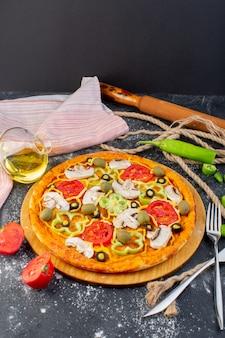 灰色の机の上に赤いトマト、グリーンオリーブ、マッシュルームとフレッシュトマトを並べた遠くのおいしいピザ