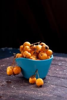 正面の遠景黄色いサクランボは茶色の木の青いボウルの中で新鮮で熟したまろやかです