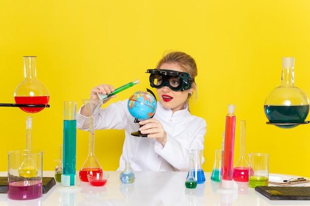 Передний дальний вид молодой женщины-химика в белом костюме с цветными растворами, работающими с ними с маской на желтом
