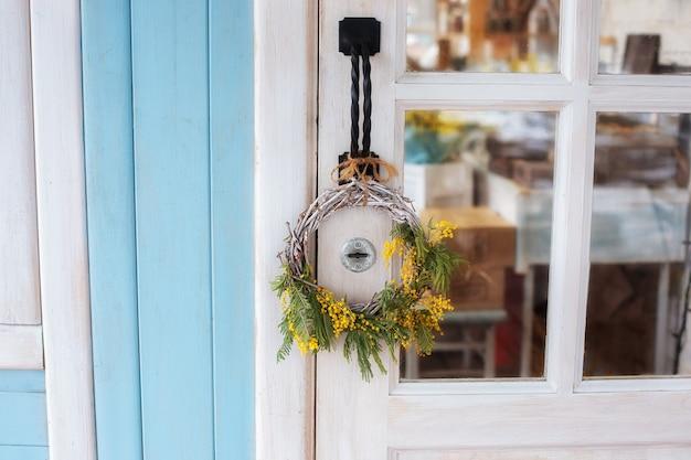 ミモザの黄色い花の花輪が付いている正面玄関。イースターリース。家の木製のドアの春の装飾。ドアに装飾的な春の花輪が付いている家の入り口。春のポーチの素朴なインテリア要素