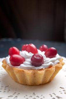Davanti vista estremamente ravvicinata deliziosa torta con crema e frutti rossi sul biscotto di frutta torta superficie scura