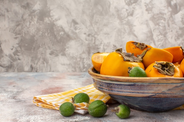 Front half view fresh persimmons in a bowl yellow kitchen towel feijoas on nude background free place
