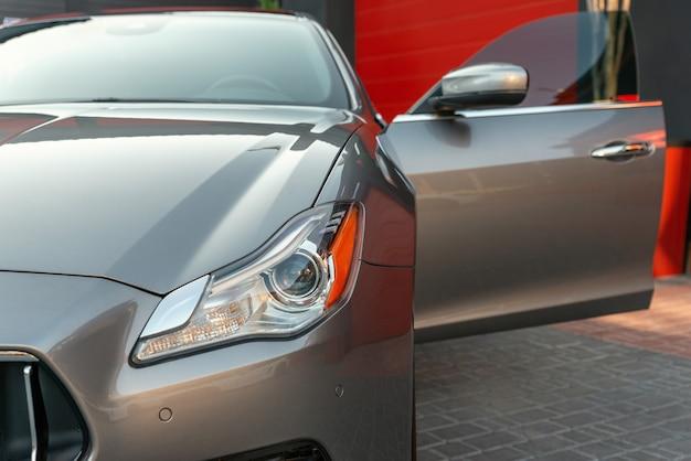 Front headlight of a metallic luxury modern car close up. car with open door.