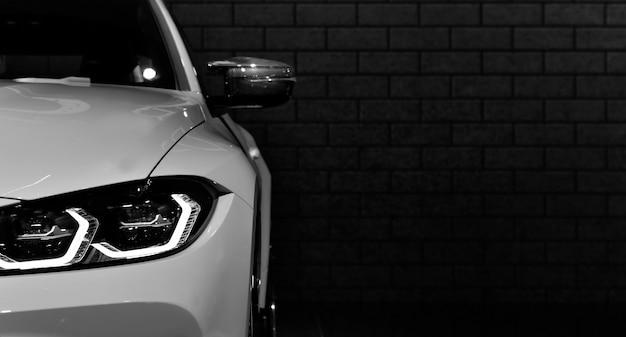Передние фары современного спортивного автомобиля черно-белые на черном фоне