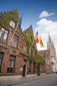 Front of the house with a sign and flags hotel in bruges