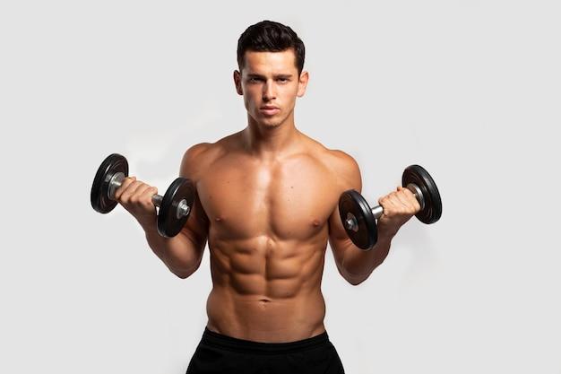 裸の胴体、ダンベルでトレーニングしているフィット感、強いハンサムな若い男の正面画像