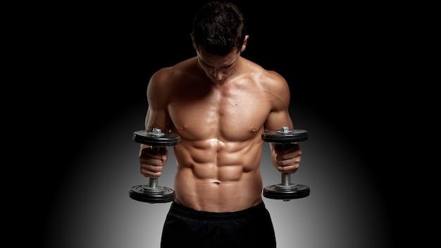 Фронтальный снимок подтянутого, сильного красивого молодого человека с обнаженным торсом, тренирующегося с гантелями