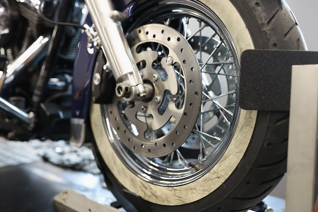 Front motorcycle wheel with shiny brake disc shock absorbers and front forks for motorcycle