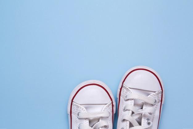 青色の背景に子供の靴の前。子供の靴、服、散歩についてのテキストのためのスペースをコピーします。