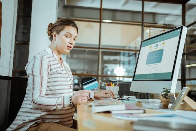 Передняя часть компьютера. беременная красивая женщина сидит перед компьютером и усердно работает