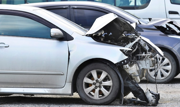 Передняя часть автомобиля серого цвета повреждена и случайно сломана.