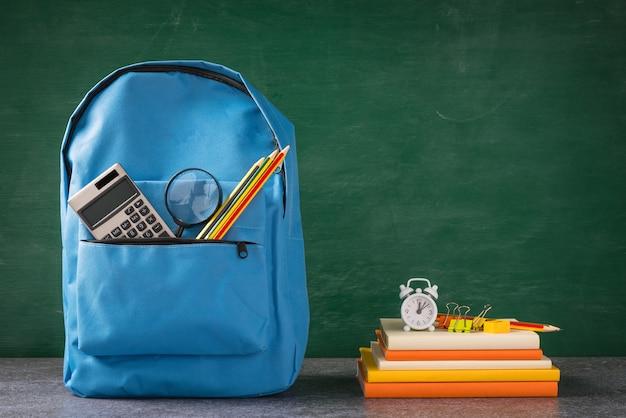 Передняя часть стильного школьного рюкзака и канцелярских принадлежностей на зеленой доске