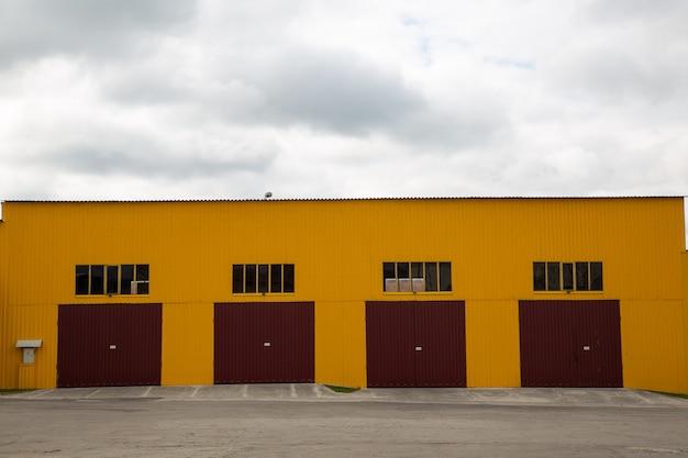 Фасад ангара для грузовых автомобилей. большие железные ворота закрыты. четыре входа.