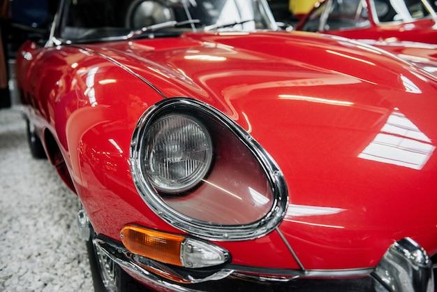 展示会で屋内に立っている赤いヴィンテージ高級車の正面